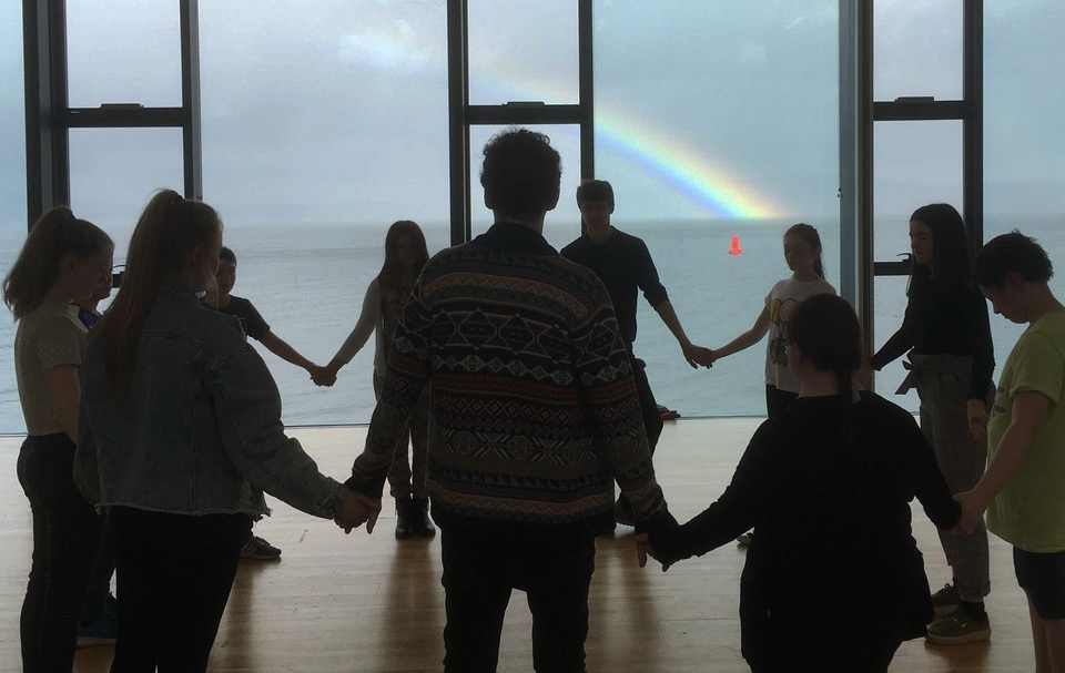 A circle of participants overlooking the Clyde estuary, with a rainbow behind.