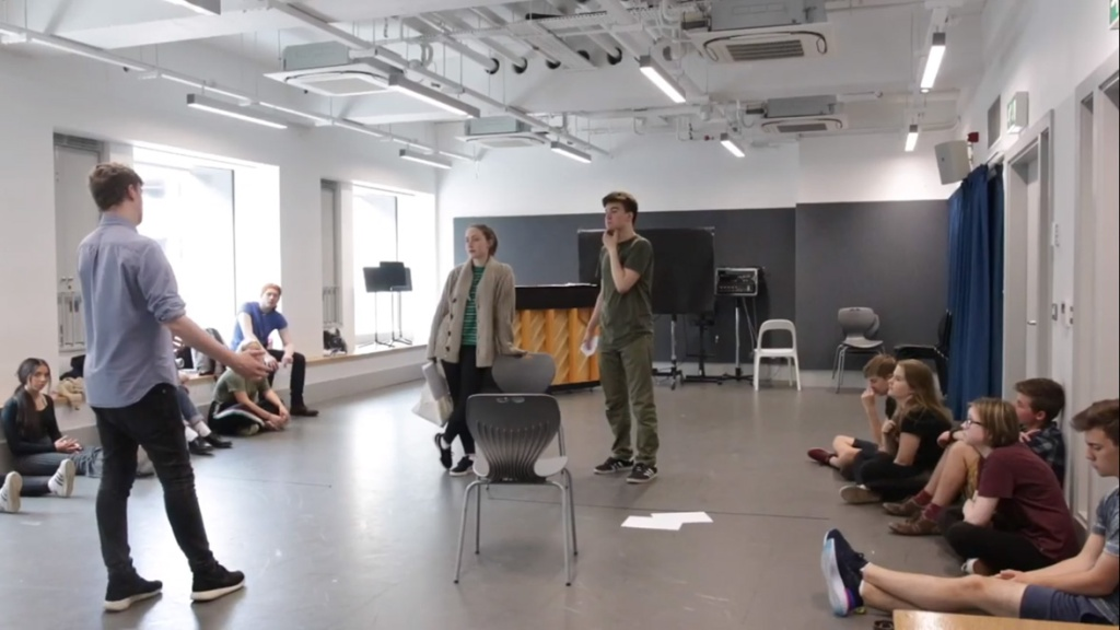 A classroom of students, with two being given instructions in the middle by Nick